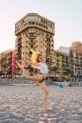 Blonde, energische Frau im Bikini und weißem Hemd auf einem Bein stehend am Strand bei Sonnenuntergang — Stockfoto