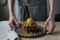 Mãos humanas segurando waffles com banana e sorvete de caril no prato — Fotografia de Stock