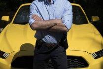 Homme confiant avec radio ensemble sur la ceinture debout avec les bras croisés contre la voiture jaune de luxe moderne — Photo de stock