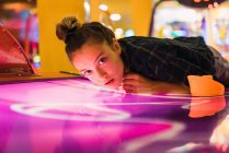 Charming young woman in casual outfit lying on shiny table for air hockey and looking at camera — Stock Photo