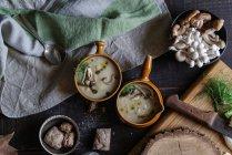 Подается в мисках вкусный грибной крем на деревенском деревянном столе с ингредиентами — стоковое фото