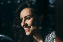 Улыбается молодой женщины, глядя из окна на солнце — стоковое фото
