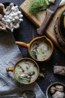 Served in bowls tasty mushroom cream on rustic wooden table with ingredients — Stock Photo