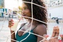Seducente sensuale nero donna avendo bevanda con paglia mentre in piedi dietro volley net sulla spiaggia — Foto stock
