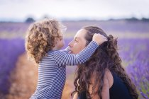 Woman and little curly daughter having fun in blooming violet lavender field — Stock Photo