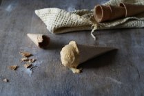 Tasty ice cream in crunchy sugar cone with empty cones on grey wooden table — Stock Photo
