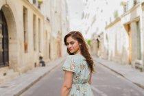 Sorrindo jovem mulher no vestido de verão andando na rua estreita e olhando sobre o ombro — Fotografia de Stock