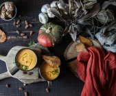 Sopa de creme de abóbora servida com peras secas em tigelas em mesa de madeira rústica com ingredientes — Fotografia de Stock
