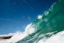 Close-up of dark ocean wave against blue sky — Stock Photo