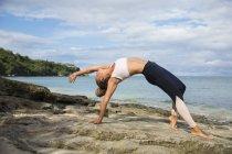 Fitte Frau in Sportbekleidung beim Yoga und Dehnen am Strand in Bali, Indonesien — Stockfoto