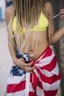 Mujer en traje de baño envuelta en bandera americana - foto de stock