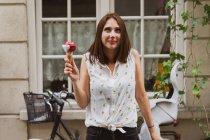 Улыбающаяся задумчивая женщина держит мороженое на улице напротив дома — стоковое фото