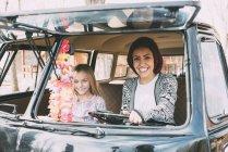 Junge Frau und blondes Mädchen sitzen im alten Auto — Stockfoto