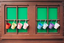 Wooden cabin windows with colorful plant pots — Stock Photo