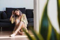Татуированная молодая женщина, прикасаясь к волосам и глядя в камеру, сидя на полу на диване — стоковое фото