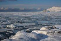 Enormi blocchi di ghiaccio sull'acqua con la nave sullo sfondo, Svalbard, Norvegia — Foto stock