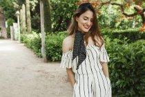 Улыбающаяся расслабленная женщина в полосатом комбинезоне гуляет в парке — стоковое фото