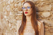 Elegante donna premurosa in occhiali appoggiato sulla parete di pietra all'aperto — Foto stock