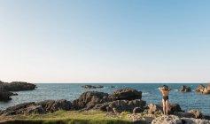 Femme en maillot de bain et chapeau debout sur l'herbe sur la côte et bénéficiant d'une vue sur la mer par une journée ensoleillée — Photo de stock