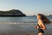 Jeune femme en maillot de bain courant près de la mer — Photo de stock