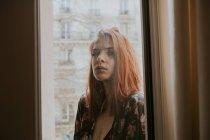 Donna in piedi alla finestra — Foto stock
