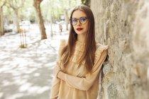 Jovem mulher pensativa em blusa elegante e óculos apoiados na parede de pedra na rua e olhando para a câmera — Fotografia de Stock