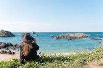 Frau in schwarzem Outfit und Hut sitzt auf Gras an der Küste und genießt den Blick auf das Meer — Stockfoto