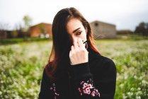 Sensuale giovane donna in abito nero che tiene gli occhiali e in piedi in campo verde — Foto stock