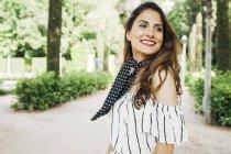 Sorrindo mulher elegante com cabelo castanho andando no parque — Fotografia de Stock