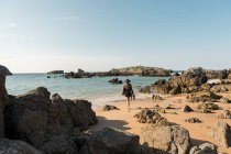 Woman in hat walking on sandy shore amidst boulders towards sea — Stock Photo