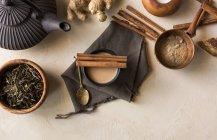 Чай с молоком, корицей, имбирем, белым перцем и кардамоном на бежевой поверхности — стоковое фото