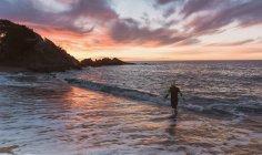 Triathlete walking out of sea — Stock Photo