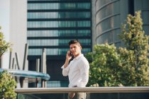 Young man talking on smartphone against modern skyscraper — Stock Photo