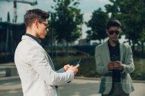 Молодой бизнесмен, использующий смартфон возле стеклянной стены — стоковое фото