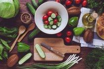 De cima variedade de vegetais maduros vermelhos e verdes, salada em tigela e tábua de corte de madeira . — Fotografia de Stock