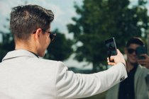 Стильний молодий підприємець беручи selfie з смартфон поблизу скляною стіною — стокове фото