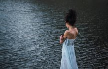 Young woman in white dress standing alone on shore of lake — Stock Photo