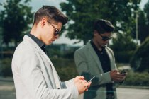 Young businessman using smartphone near glass wall — Stock Photo