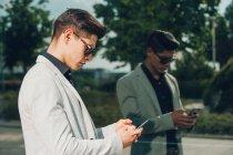Giovane uomo d'affari utilizzando smartphone vicino alla parete di vetro — Foto stock