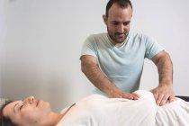 Terapeuta facendo terapia alternativa trattamento del corpo per stimolare i tessuti del corpo in sala massaggi — Foto stock