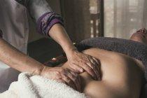 Терапевт делает восточный массаж женщине в массажном кабинете — стоковое фото
