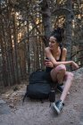 Charming woman with backpack and cup resting in forest in mountains — Stock Photo