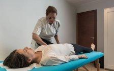 Терапевт, занимающийся лечением тела для стимулирования проблем с телом в массажном кабинете — стоковое фото