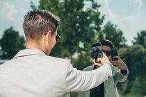 Elegante giovane uomo d'affari che prende selfie con smartphone vicino alla parete di vetro — Foto stock