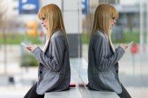 Giovane donna bionda appoggiata al muro sulla strada e utilizzando lo smartphone — Foto stock