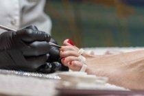 Manicure feminino fazendo pedicure ao cliente no salão de beleza — Fotografia de Stock