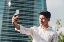 Young businessman taking selfie with smartphone against modern building — Stock Photo