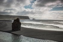 Rock en la playa con acantilados bajo el espectacular cielo, Islandia - foto de stock