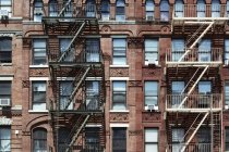 Escaliers métalliques sur la façade de brique immeuble sur la rue, New York, é.-u. — Photo de stock