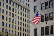 Bandera de Estados Unidos colgando en la fachada de un edificio moderno en la calle de Nueva York, Estados Unidos - foto de stock